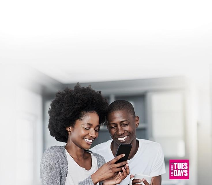 Dos personas sonriendo y mirando un teléfono juntas.